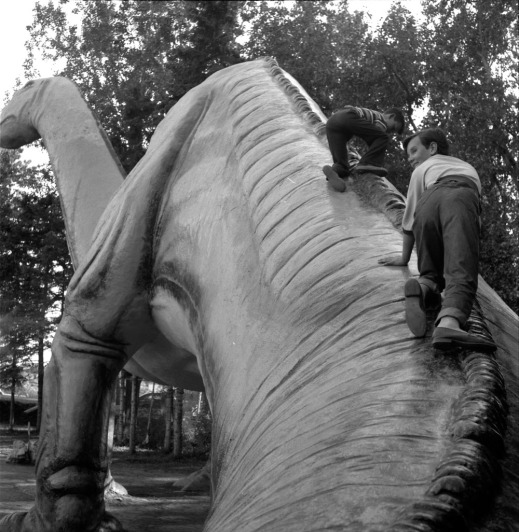 A black-and-white photograph of two children climbing up a large model dinosaur.