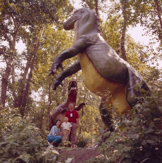 A woman, child and man stand under a large model of a dinosaur, surrounded by trees. The group is looking toward another dinosaur model.
