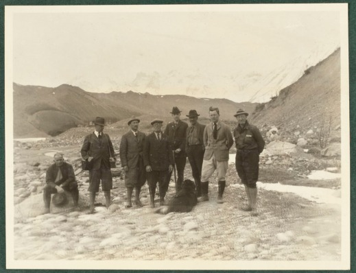 A sepia coloured photograph of a group of men with Mount Logan in the background.