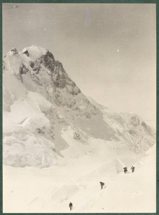 A photograph of Mount Logan with four climbers in the foreground.