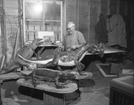 A man is in a garage or workshop, standing near three sculptures of prehistoric reptiles and holding a can of paint and a paintbrush in his hands.