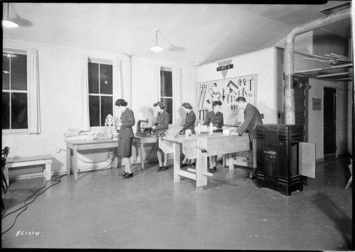 A black-and-white photo of four women and a man in a shop with tools and tables. There are three windows and a sign that reads YMCA.