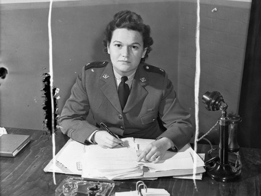 A black-and-white photograph of a woman in a military uniform looking at the camera. She has a pen in her right hand, papers on her desk and a black candlestick-style telephone to her left.