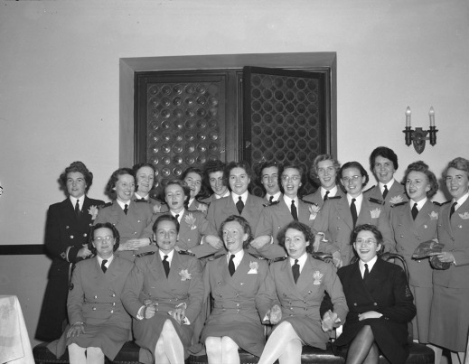 A black-and-white photo of a group of women in military uniforms smiling at the camera. There are two women in dark suits. The women in the first row are seated and holding hands. Some of the women standing in the back row have their arms linked.